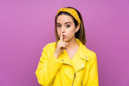 Young woman over purple background doing silence gesture