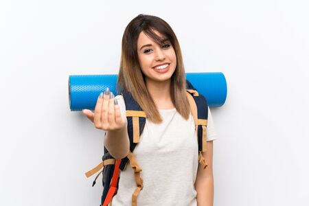 Young traveler woman over white background inviting to come with hand. Happy that you came Banco de Imagens