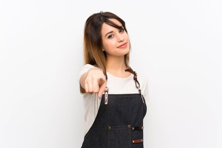 Young woman with an apron points finger at you with a confident expression