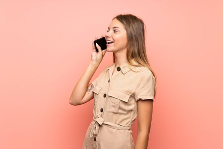 Lithuanian blonde girl over isolated pink background keeping a conversation with the mobile phone Stok Fotoğraf