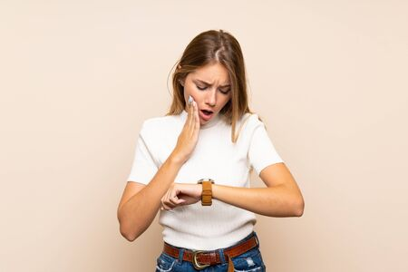 Young blonde woman over isolated background with wrist watch and surprised
