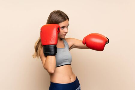 Young blonde girl with boxing gloves over isolated background Banco de Imagens