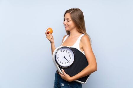 Young blonde girl with weighing machine and with an apple over isolated blue white background