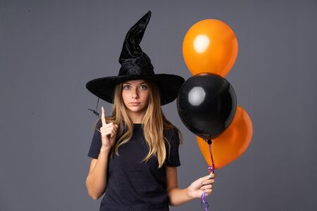 Young witch holding black and orange air balloons pointing with the index finger a great idea