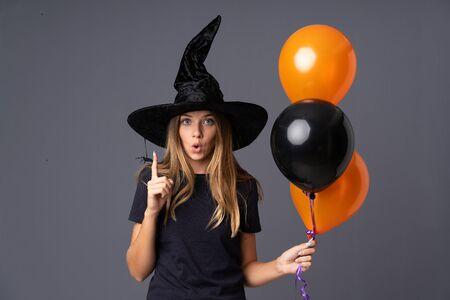 Young witch holding black and orange air balloons with surprise facial expression