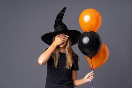 Young witch holding black and orange air balloons covering eyes by hands