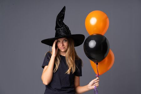 Young witch holding black and orange air balloons unhappy and frustrated with something. Negative facial expression
