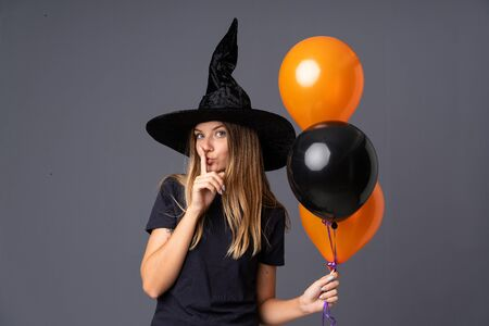 Young witch holding black and orange air balloons doing silence gesture