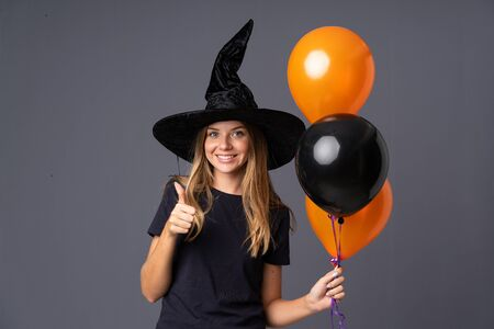 Young witch holding black and orange air balloons giving a thumbs up gesture