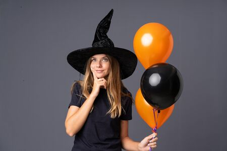 Young witch holding black and orange air balloons thinking an idea
