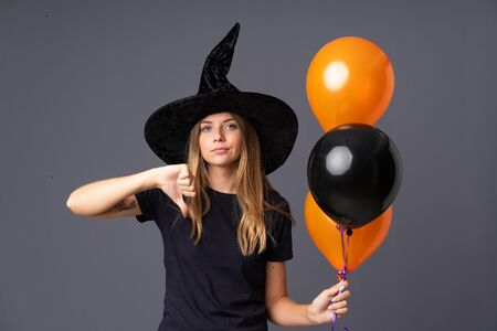 Young witch holding black and orange air balloons showing thumb down sign