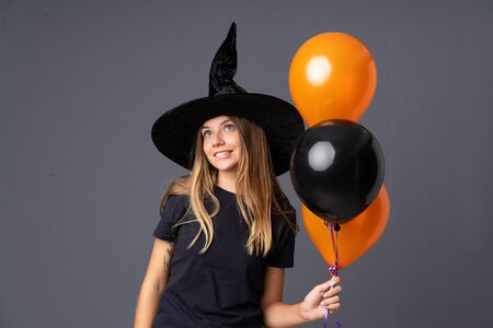 Young witch holding black and orange air balloons laughing and looking up