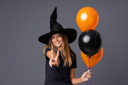 Young witch holding black and orange air balloons smiling and showing victory sign