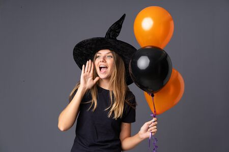 Young witch holding black and orange air balloons shouting with mouth wide open