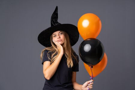 Young witch holding black and orange air balloons unhappy and frustrated