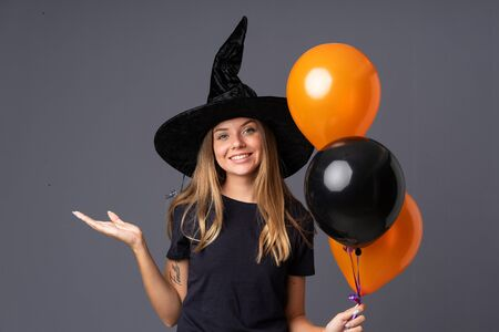 Young witch holding black and orange air balloons holding copyspace imaginary on the palm