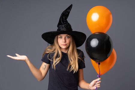 Young witch holding black and orange air balloons having doubts with confuse face expression