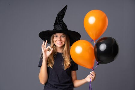 Young witch holding black and orange air balloons showing an ok sign with fingers