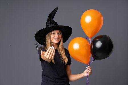Young witch holding black and orange air balloons inviting to come