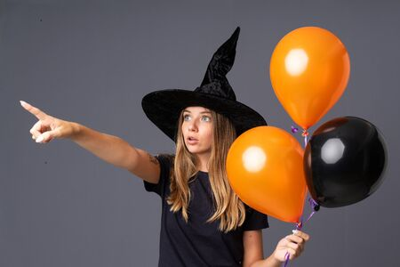 Young witch holding black and orange air balloons pointing away
