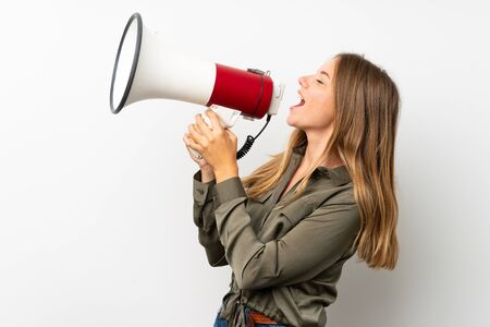 Lithuanian blonde girl over isolated white background shouting through a megaphone