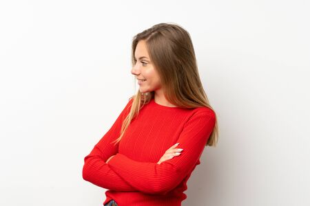 Young blonde woman with red sweater over isolated white background looking to the side