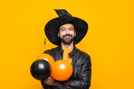 Man with witch hat holding black and orange air balloons for halloween party keeping the arms crossed in frontal position