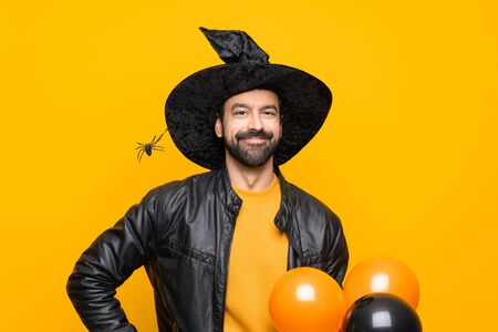 Man with witch hat holding black and orange air balloons for halloween party posing with arms at hip and smiling Imagens