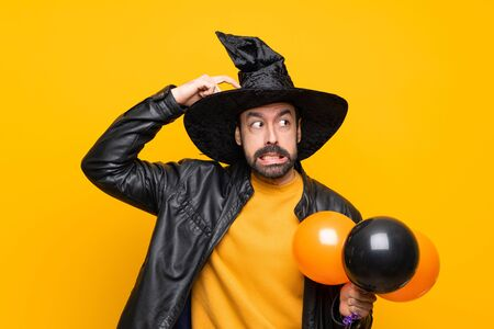 Man with witch hat holding black and orange air balloons for halloween party having doubts while scratching head Stok Fotoğraf