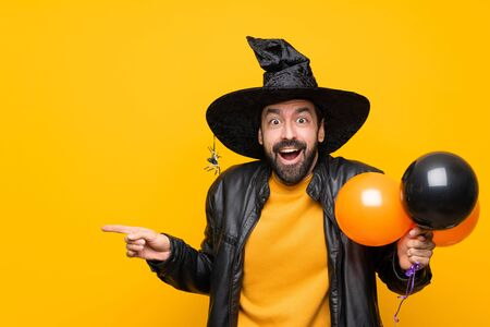 Man with witch hat holding black and orange air balloons for halloween party surprised and pointing finger to the side