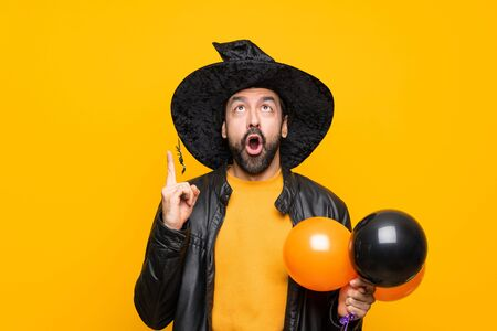 Man with witch hat holding black and orange air balloons for halloween party pointing up and surprised