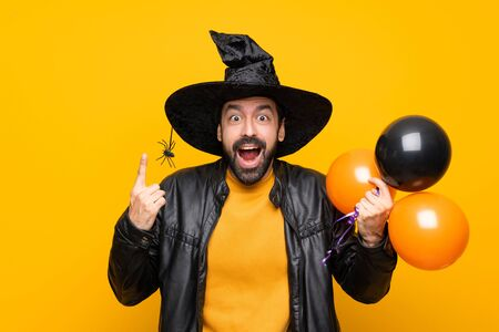 Man with witch hat holding black and orange air balloons for halloween party pointing up a great idea Imagens