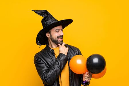 Man with witch hat holding black and orange air balloons for halloween party looking to the side Stok Fotoğraf
