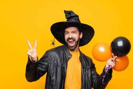 Man with witch hat holding black and orange air balloons for halloween party showing victory sign with both hands