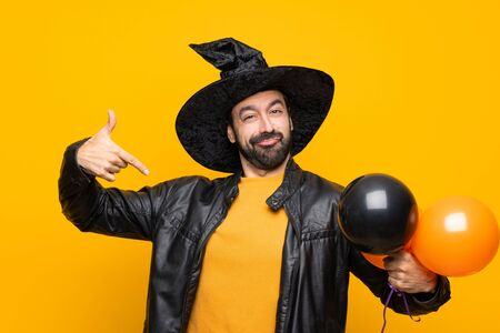 Man with witch hat holding black and orange air balloons for halloween party proud and self-satisfied