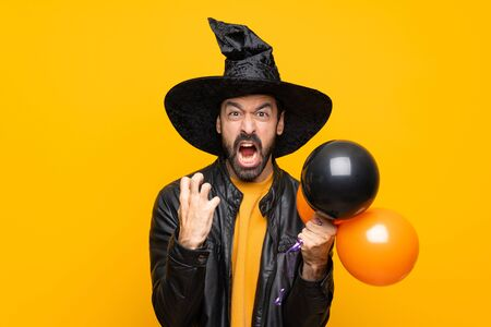 Man with witch hat holding black and orange air balloons for halloween party frustrated by a bad situation