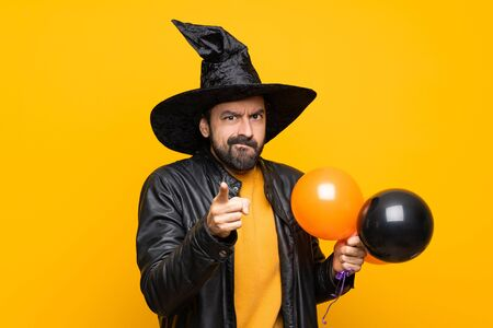 Man with witch hat holding black and orange air balloons for halloween party frustrated and pointing to the front