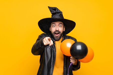 Man with witch hat holding black and orange air balloons for halloween party surprised and pointing front