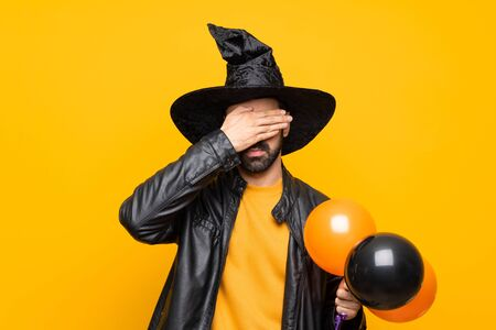 Man with witch hat holding black and orange air balloons for halloween party covering eyes by hands. Do not want to see something