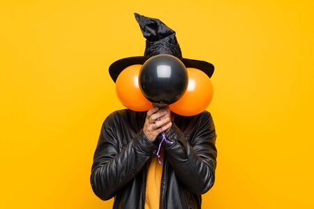 Man with witch hat holding black and orange air balloons for halloween party covering eyes by hands