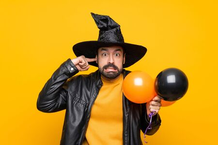 Man with witch hat holding black and orange air balloons for halloween party frustrated and covering ears Stok Fotoğraf