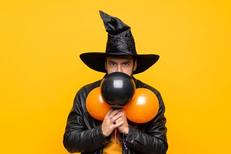 Man with witch hat holding black and orange air balloons for halloween party covering mouth with hands