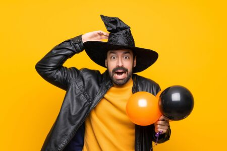 Man with witch hat holding black and orange air balloons for halloween party frustrated and takes hands on head