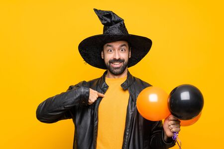 Man with witch hat holding black and orange air balloons for halloween party with surprise facial expression