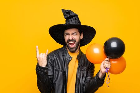 Man with witch hat holding black and orange air balloons for halloween party making rock gesture