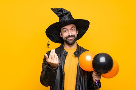 Man with witch hat holding black and orange air balloons for halloween party inviting to come with hand. Happy that you came