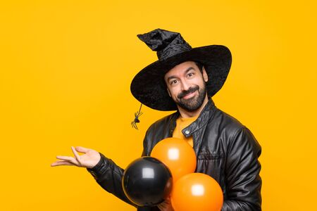 Man with witch hat holding black and orange air balloons for halloween party extending hands to the side for inviting to come