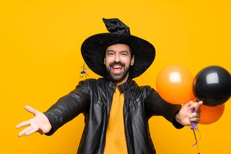 Man with witch hat holding black and orange air balloons for halloween party presenting and inviting to come with hand