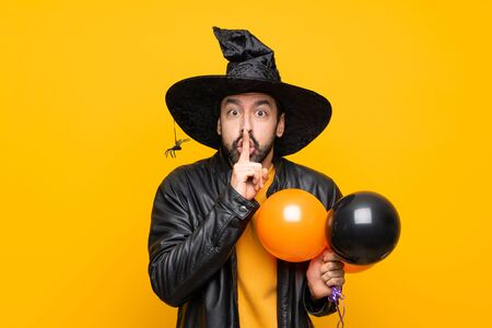 Man with witch hat holding black and orange air balloons for halloween party showing a sign of silence gesture putting finger in mouth