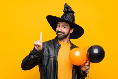 Man with witch hat holding black and orange air balloons for halloween party showing and lifting a finger in sign of the best